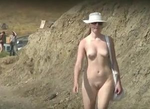 Naturist lady ambles on the beach just..